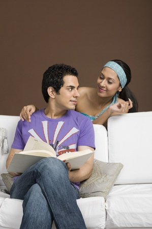 couple on couch: Man holding a book and looking at his girlfriend