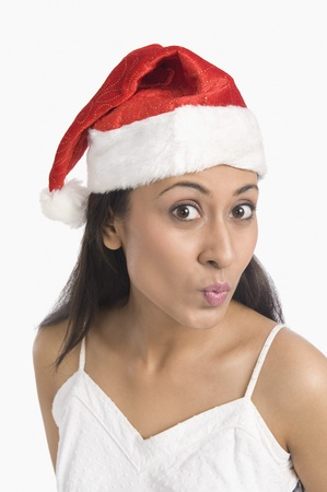 puckering: Close-up of a woman wearing a Santa hat and puckering