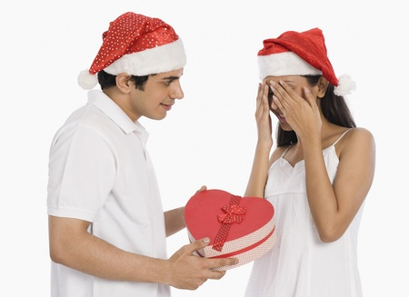 covering: Man giving a Christmas present to his girlfriend LANG_EVOIMAGES