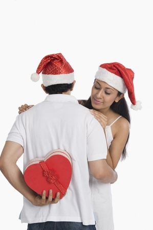 Man hiding a Christmas present to surprise his girlfriend Stock Photo - 10124425