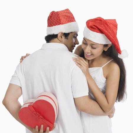 Man verbergen van een kerstcadeau voor zijn vriendin te verrassen Stockfoto