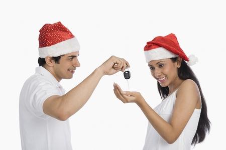 Man giving car key as a Christmas present to his girlfriend Stockfoto
