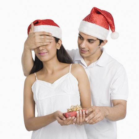 covering: Man covering his girlfriends eyes and giving a Christmas present LANG_EVOIMAGES