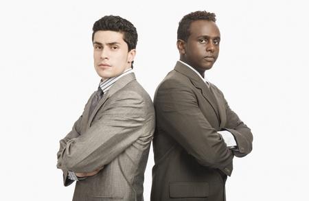 business rival: Dos hombres de negocios de pie espalda con espalda