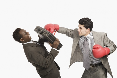 cut the competition: Businessman defending himself from the punch of his colleague