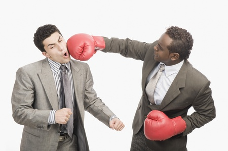 cut the competition: Businessman punching his co-worker with boxing gloves