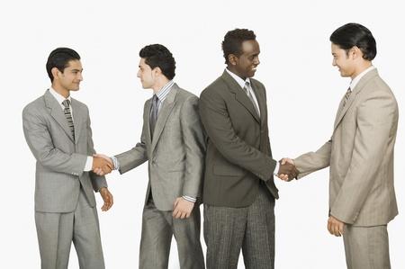 congratulating: Four businessmen shaking hands