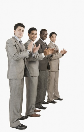 Portrait of four businessmen applauding
