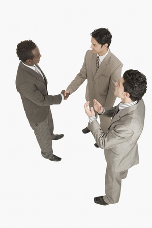 Two businessmen shaking hands with another businessman clapping Stock Photo - 10125581