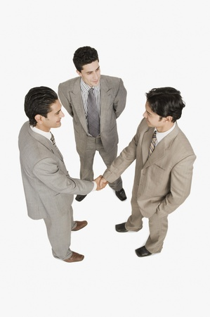 shaking out: Two businessmen shaking hands with another businessman standing beside them