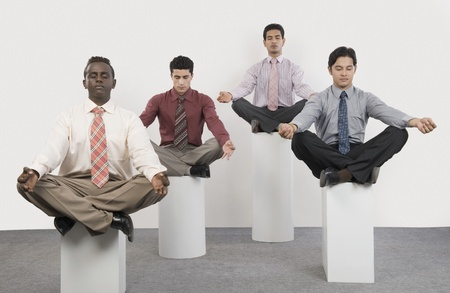 sports attire: Four businessmen practicing yoga
