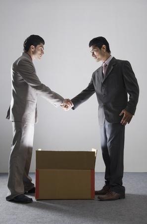 Twee zakenlieden schudden handen over een verlichte kartonnen doos Stockfoto