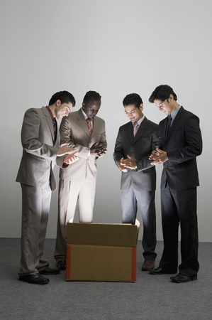 Businessmen applauding over an illuminated cardboard box