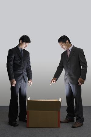 Two businessmen looking into an illuminated cardboard box Foto de archivo