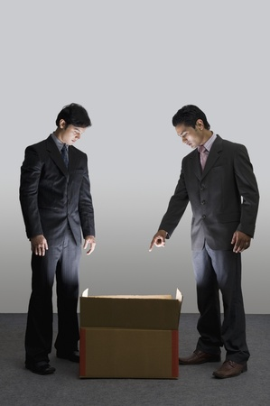 Two businessmen looking into an illuminated cardboard box LANG_EVOIMAGES