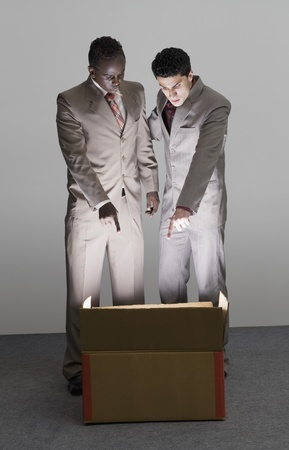 cardboard only: Two businessmen looking into an illuminated cardboard box LANG_EVOIMAGES