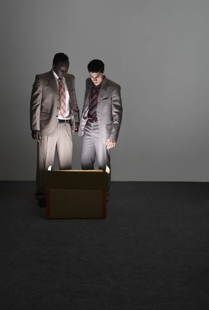 Two businessmen looking into an illuminated cardboard box Imagens