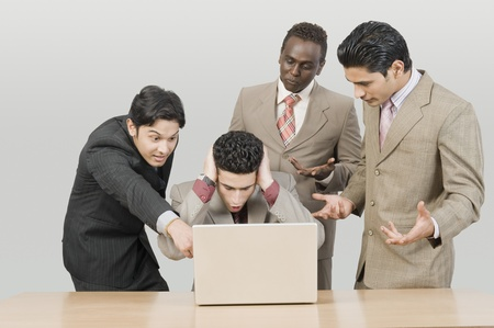 Four businessmen looking shocked in front of a laptop Фото со стока