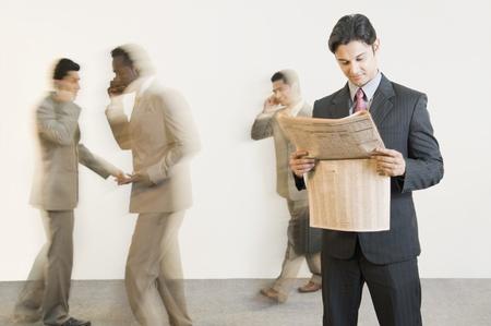 사업가 백그라운드에서 그의 동료와 함께 신문을 읽는