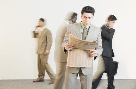 Businessman reading a newspaper with his colleagues in the background Stock Photo - 10124751