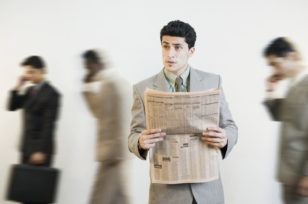 communication: Businessman reading a newspaper with his colleagues in the background LANG_EVOIMAGES