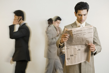 Businessman reading a newspaper with his colleagues in the background Stock Photo - 10125189