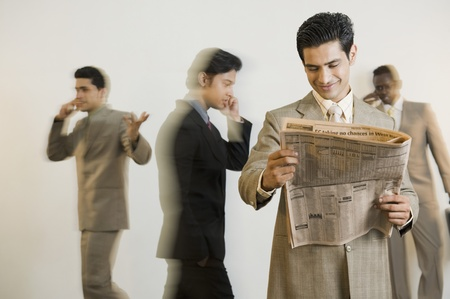 news stand: Businessman reading a newspaper with his colleagues in the background LANG_EVOIMAGES
