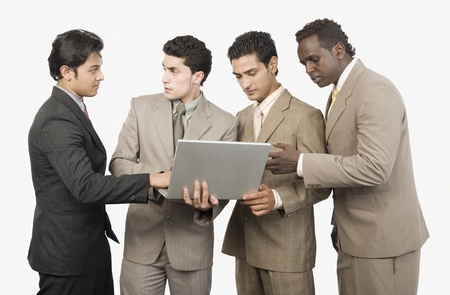Four businessmen standing with a laptop Stock Photo - 10166463