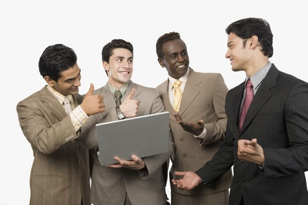 Four businessmen smiling in front of a laptop Stock Photo - 10169295