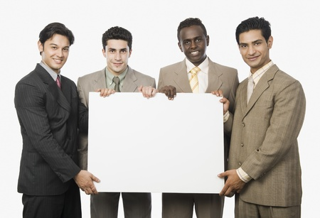 four person only: Portrait of four businessmen showing a blank placard