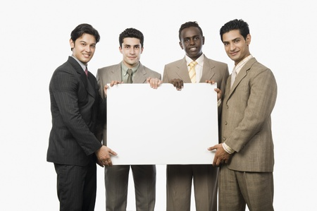 Portrait of four businessmen showing a blank placard Stock Photo - 10125202