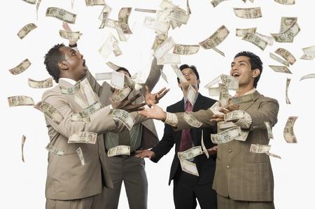 Banknotes falling over four businessmen Standard-Bild