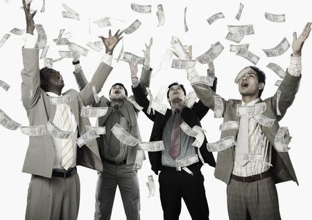Banknoten fallen über vier Geschäftsleute Standard-Bild - 10166533