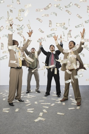 Banknotes falling over four businessmen Stock Photo - 10169067
