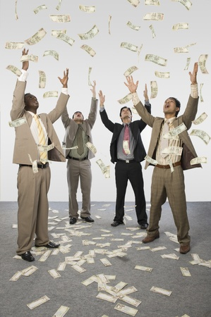 Four businessmen standing with arms raised with currency notes scattered on the floor