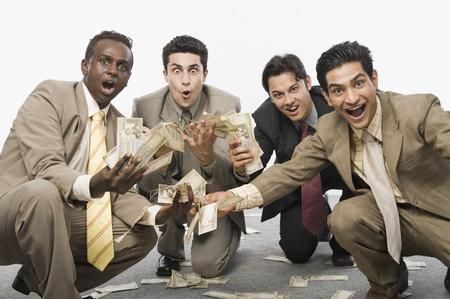 Portrait of four businessmen crouching and holding currency notes Standard-Bild