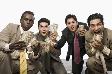 Porträt von vier Geschäftsleuten hocken und halten Banknoten Standard-Bild - 10169235