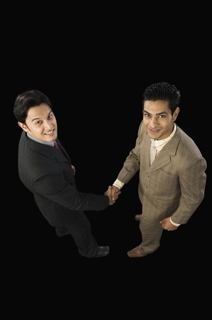 shaking out: High angle view of two businessmen shaking hands LANG_EVOIMAGES