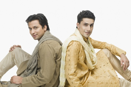 kurta: Two men sitting back to back and smiling LANG_EVOIMAGES