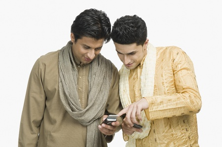 telecommunicating: Two men text messaging on mobile phones LANG_EVOIMAGES