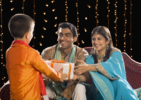 family sofa: Couple giving Diwali gift to their son