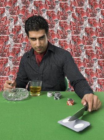 casino table: Man smoking and drinking at a casino table