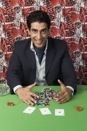 Portrait of a man smiling and collecting won gambling chips Stock Photo - 10169045