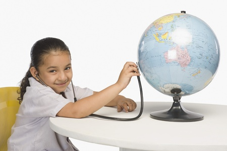Girl examining a globe with a stethoscope Stock Photo - 10124525