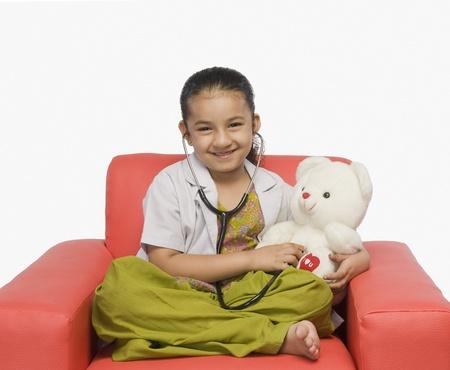 Girl examining a teddy bear with a stethoscope Stock Photo - 10125036