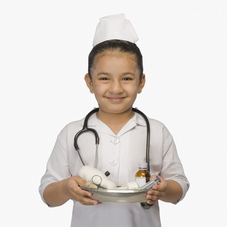 Girl dressed as a nurse and holding a tray of medicines and smiling Stock Photo - 10125619