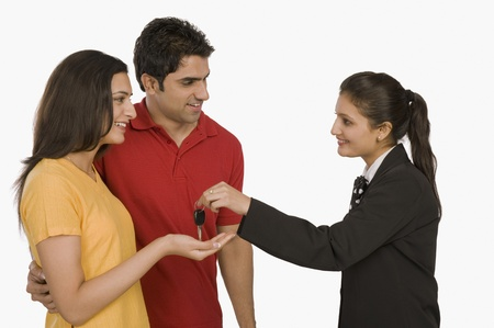 sales person: Businesswoman giving a car key to a woman