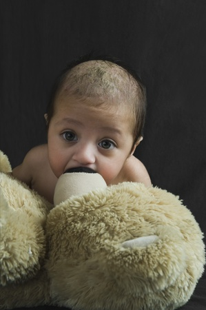 Close-up of a baby boy playing with a teddy bear