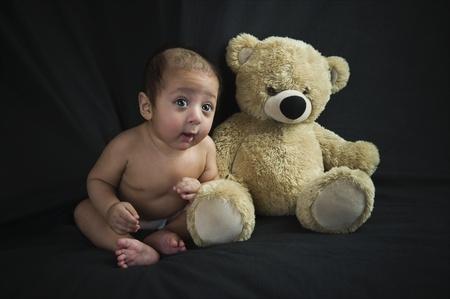 Baby boy sitting with a teddy bear Stock Photo