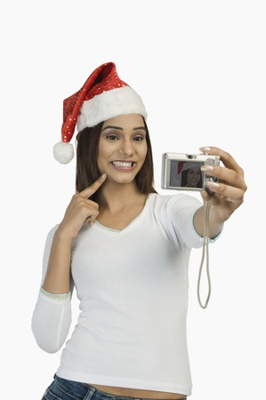 Woman taking a picture of herself with a digital camera Banco de Imagens